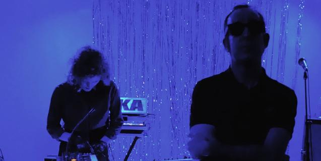 Los dos miembros de la banda uno de pie y otro tocando el sintetizador en un espacio bañado en luz azul
