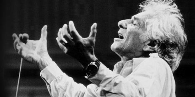 Leonard Bernstein with his hands in the air, moved by the music.