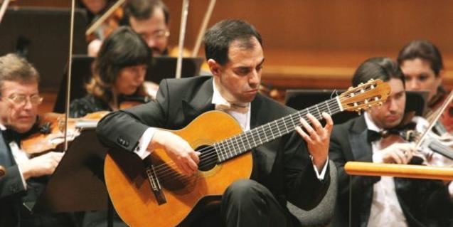 El guitarrista Rolando Saad amb l'orquestra tocant al Palau de la Música.
