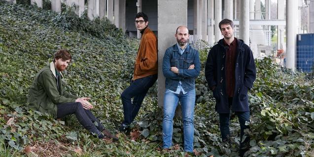 Los integrantes del grupo retratado al aire libre y rodeados de plantas