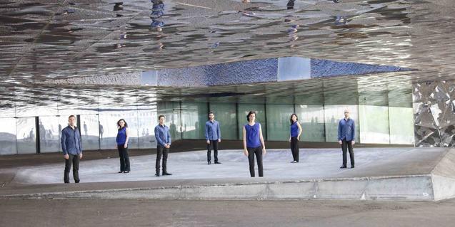Los miembros de la formación retratados en un espacio con un techo reflectante