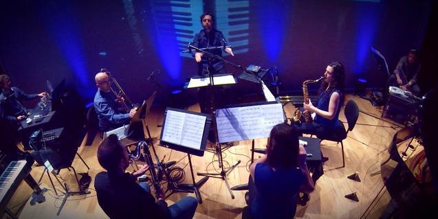 Los miembros de la formación colocados en círculo durante la interpretación de una pieza musical