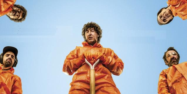 Los miembros de la banda vestidos de color naranja con palas en las manos como si acabaran de enterrar a alguien