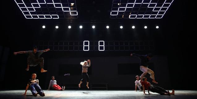 Uns artistes evolucionen per l'escenari amb una escenografia de llum al darrere