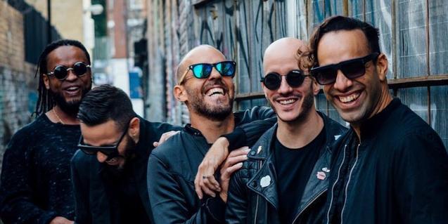 Cinco de los integrantes de la formación retratados mientras se rien en un callejón de una ciudad