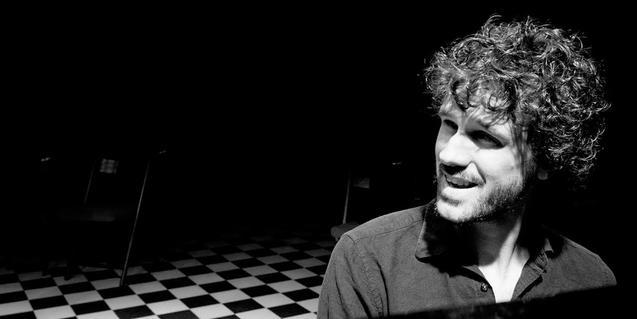 Retrato en blanco y negro del músico sentado al piano