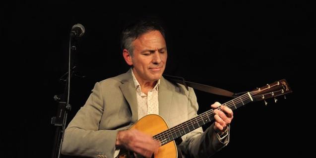 El músic barceloní retratat tocant una guitarra sobre l'escenari