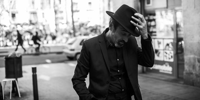 Retrat en blanc i negre de l'artista passejant per un carrer de Barcelona i amb un barret