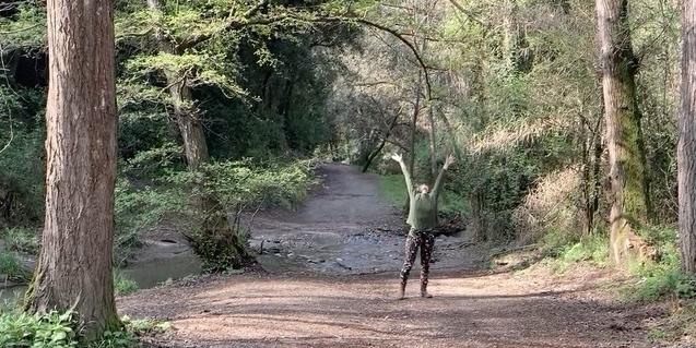 Una de les participants en el vídeo balla envoltada d'arbres en un bosc