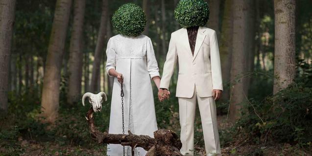 Els dos intèrprets vestits de blanc i amb una bola vegetal com a cap retratats en un bosc