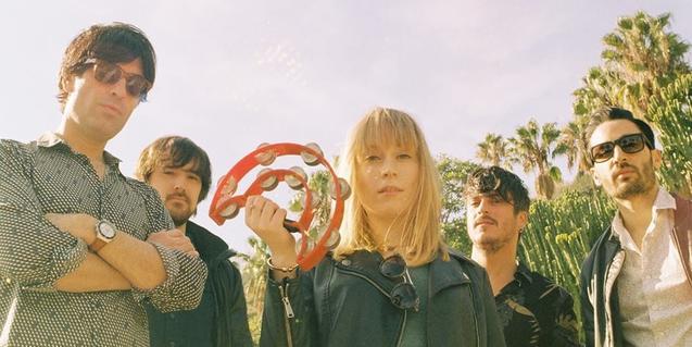 La vocalista del grup amb una pandereta a la mà i envoltada de la resta de músics de la banda