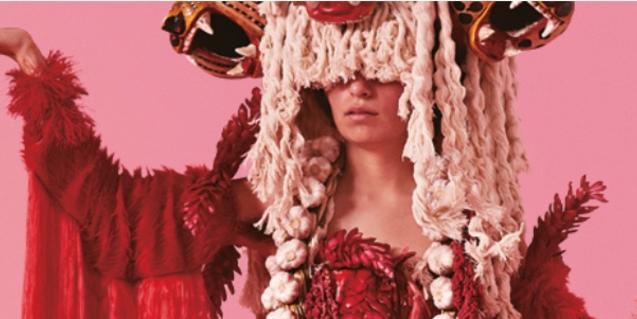 Una noia amb un vestit llarg i un barret extravagant que li tapa la cara en una de les imatges del Grec d'enguany