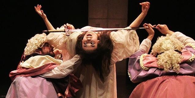 Una actriz suspendida cabeza abajo en un momento de la representación