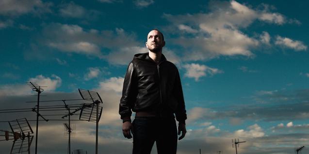 El músic Oscar D'Aniello retratat contra un cel blau amb antenes de televisió de fons