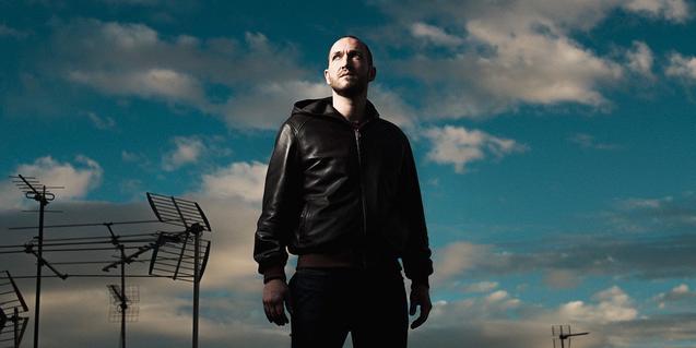 Retrato del músico Oscar D'Aniello contra un cielo lleno de antenas de televisión