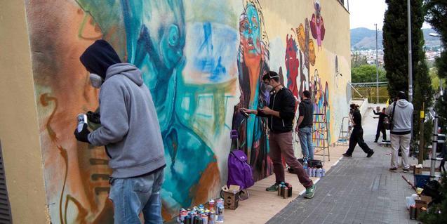 Un grup de joves fa un grafiti de manera col·lectiva