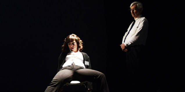 Retrato de los dos actores con él de pie y ella sentada en una silla