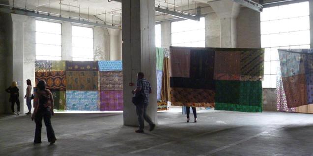 Una fotografia d'un gran espai industrial buit amb unes robes penjades a l'interior