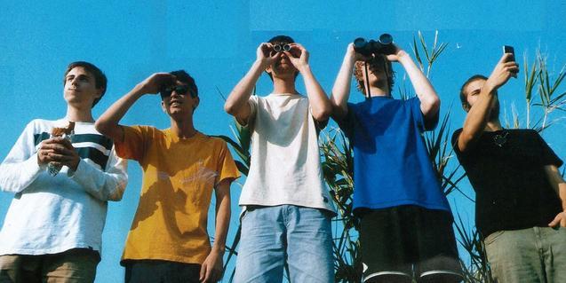 Los miembros de esta banda retratados en exteriores mirando con unos prismáticos