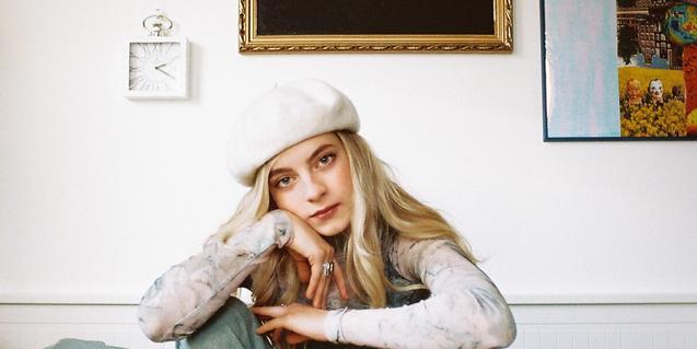 Retrato de la artista húngara con una gorra blanca y sujetándose la cabeza con una mano