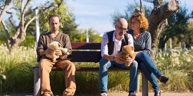 Un padre biológico y unos padres de acogida, sentados en un banco del parque con un oso de peluche en la falda