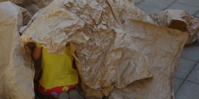 Fotografia del taller, un infant jugant amb paper d'embalar