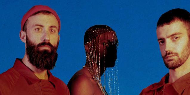 Los tres miembros de la banda retratados en plano medio con dos de los músicos llevando tocados de inspiración africana