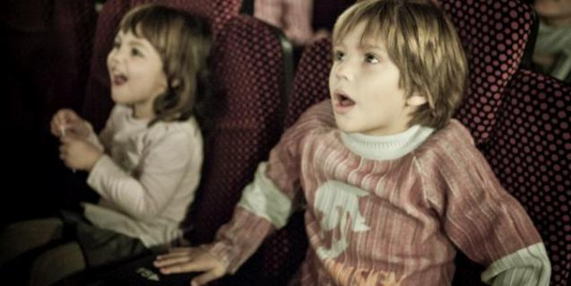 Two children with a look of surprise on their faces sitting in the cinema.