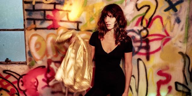 L'artista retratada davant d'un mur ple de grafiti