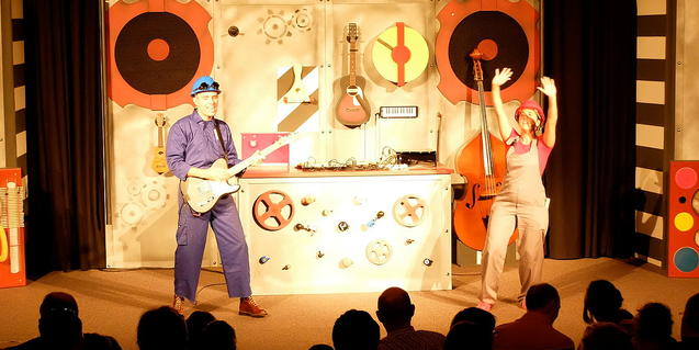 Imagen del espectáculo con los dos protagonistas en el escenario rodeados por los instrumentos.