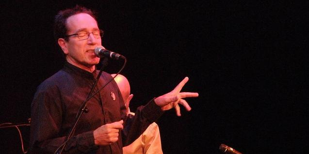 El músic expert en folk cantant amb els ulls tancats davant un micròfon