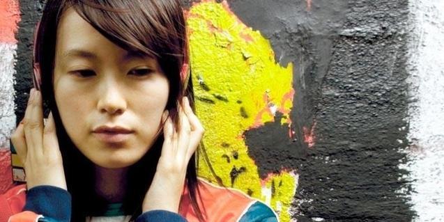 Una chica escucha música con unos auriculares en el cartel que anuncia esta película china