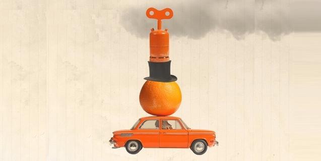 Un coche de juguete de color naranja con una naranja y una bombona de gas butano encima
