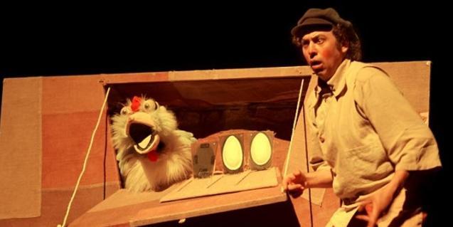 Actor con un títere de gallina en la granja