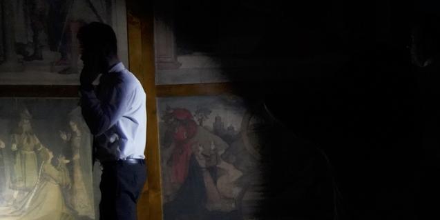 La imagen de un visitante que mira unos cuadros en penumbra ilustra un proyecto artístico centrado en  el MNAC