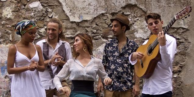 Los cinco músicos de la formación retratados tocando música ante un muro desconchado