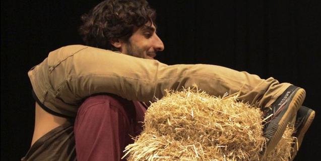 Uno de los artistas carga a la espalda a su compañera mientras lleva en las manos una paca de paja