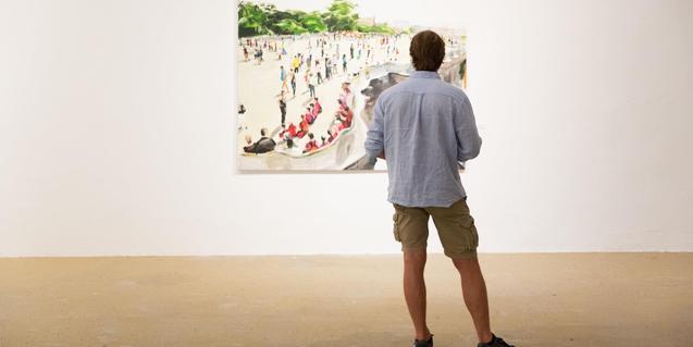 Un visitant es mira un quadre durant una exposició al centre