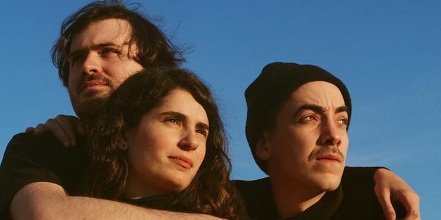 Los tres integrantes de la formación abrazados y retratados al aire libre