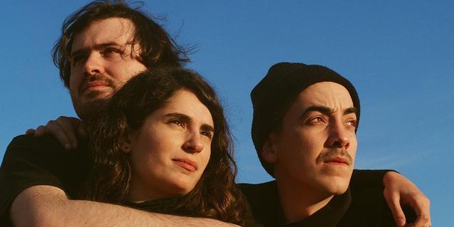 Els tres membres de la banda barcelonina retratats abraçant-se en un espai exterior