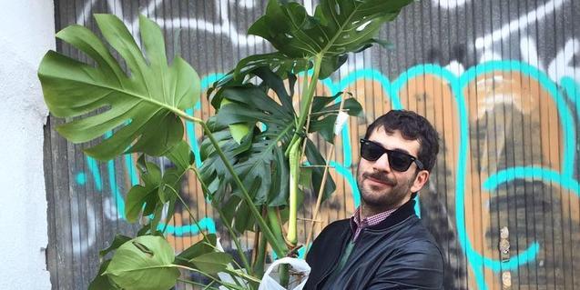 Retrat del músic amb una gran planta entre les mans retratat davant d'un grafiti de colors vius