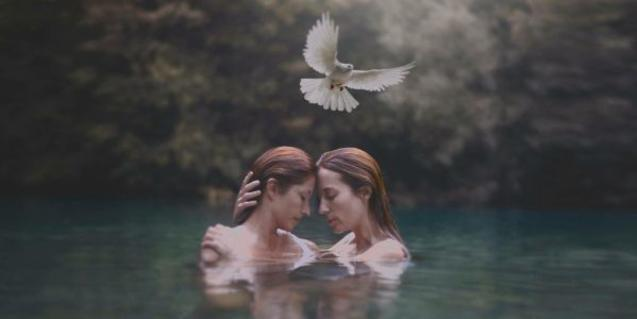 Two women embracing in a lake, a white dove flies over their heads..