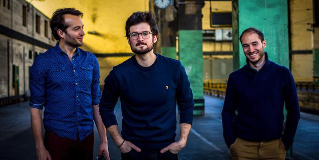 Els tres membres de la banda retratats a l'interior d'un espai fabril