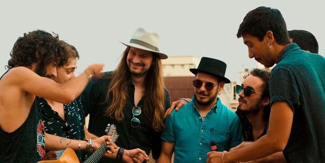 Retrat dels membres de la banda en exteriors amb gorres i barrets i una guitarra entre les mans