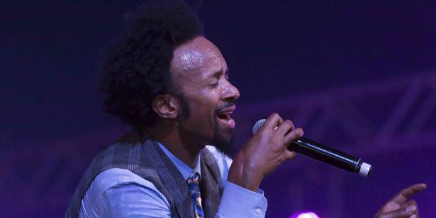 Retrat de l'artista en plena actuació amb un micròfon a la mà