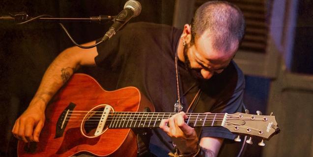 El músic retratat en plena actuació mentre toca la guitarra