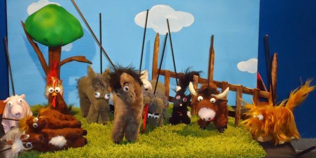Peluixos d'animals de granja en un escenari de titelles