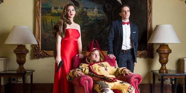 Una imagen del espectáculo con un actor y una actriz de pie y vestidos de fiesta y un tercer personaje disfrazado y sentado en una butaca