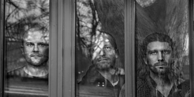 ELs tres integrants de la formació vistos a través dels vidres d'una finestra