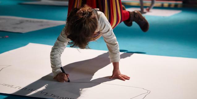 Fotografía de un niño pintando des de una hamaca de la edición del año pasado